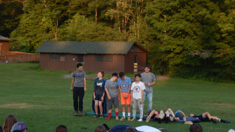 Cabin group standing in a row in front of a mattress. Half the campers have fallen backward onto the mattresses.