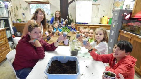 Campers seated at a table holding up plants they have potted to the camera and smiling.