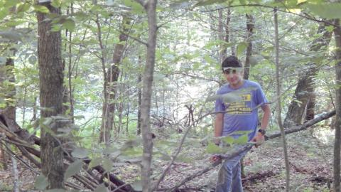 Youth standing among trees in wooded area.