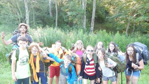 Group of campers with black handprints or marks across their faces posing with two counselors all wearing hiking backpacks.