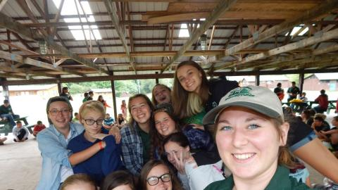 Staff taking selfie with a cabin group all smiling at camera.