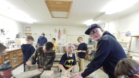 Teen looking into camera as youth around him are in various stages of woodworking projects.
