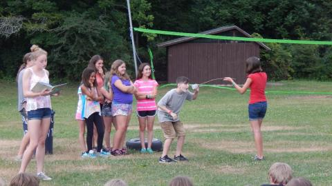 Cabin group standing together behind one camper who speaks into a cup on the end of a stick held by another camper as counselor to the side reads a story.