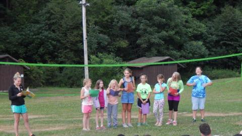 Cabin group in a line with folders as counselor to the side reads a story.