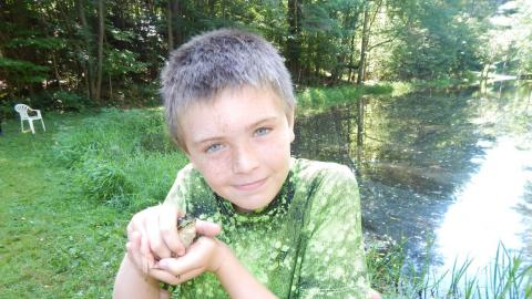 Youth holding a frog near pond.