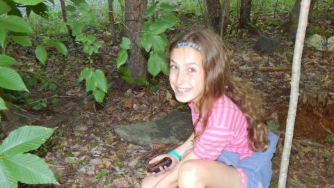 Camper in wooded are bending down to collect a geocache with GPS in their hand smiling at camera.