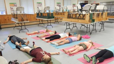 Youth in corpse pose on the floor on yoga mats.