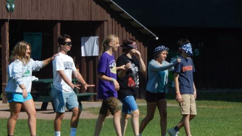 Youth lead a blindfolded partner in pairs during a trust walk.