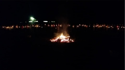 campers standing in a circle around a bonfire holding lit candles.
