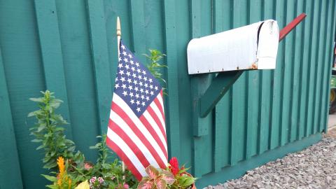 flowerpot with american flag near mailbox on green barn.