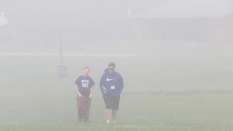 Counselor and youth walk toward the camera from across the field in thick fog.