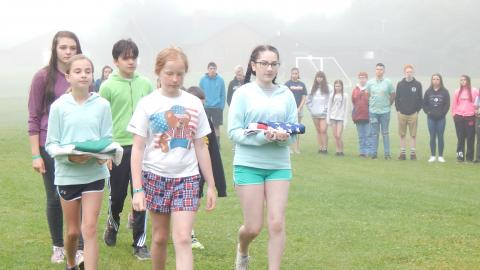 Colorguard walks toward the flagpole holding American and 4-H flags through circle of other campers.