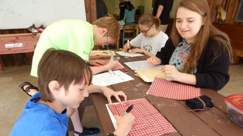 Youth sit with counselor at a table drawing 9 man morris boards on cloth with sharpie markers.