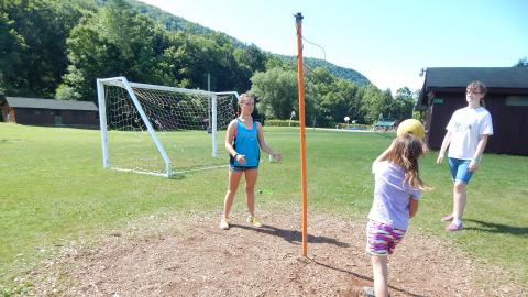 Three campers playing tether ball.