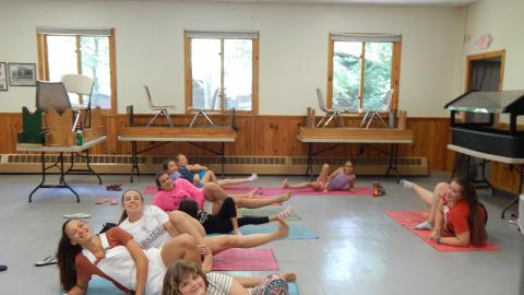 Youth laying on yoga mats with foot raised looking at the camera and smiling.