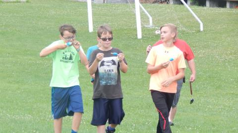 Five youth walk across the field eating popsicles.