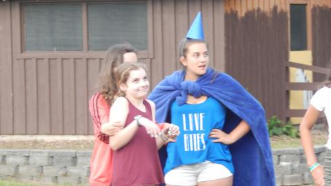 Three youth in a skit. One wears a blanket as a cape and cone on their head.