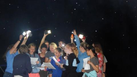 cabin group gathered together in the dark with flashlights to help them sing lyrics written on papers they are holding.