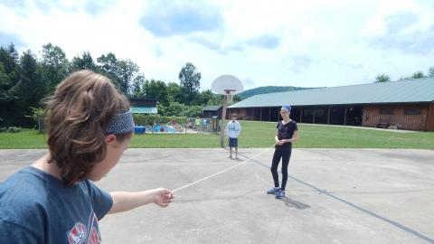 Campers on basketball court holding a string between them.