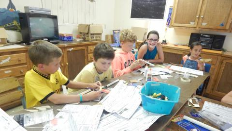 Campers seated around a table building model rockets.