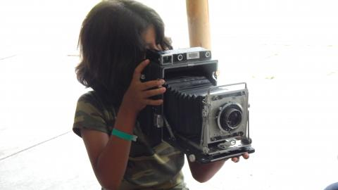 camper holding an old fashioned camera and looking through the lens.