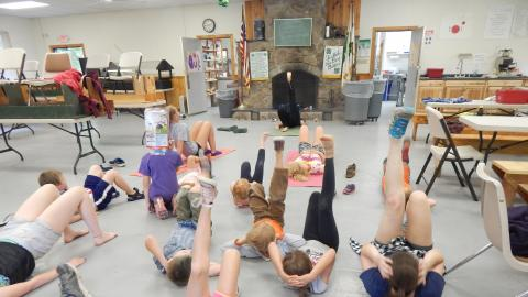 Campers lay on dining hall floor with hands behind head a feet raised up in the air following the lead of a counselor.