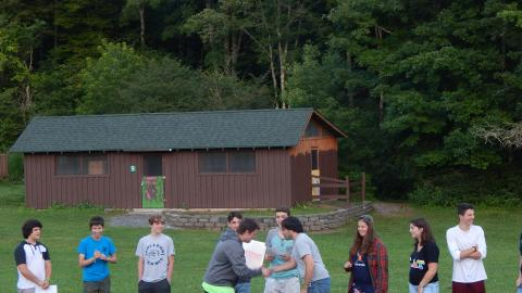 Campers stand in a line with counselors during a skit for the rest of camp seated in front.