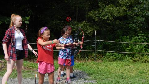Youth stand on firing line with bows drawn as counselor looks over them.
