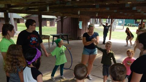 Day campers in a circle holding hands and passing a hula hoop around as a counselor times them with a stopwatch.