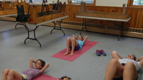 Campers doing crunches on yoga mats.