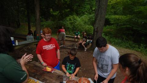 Campers wait in line to add marshmallows to their banana near a fire pit.