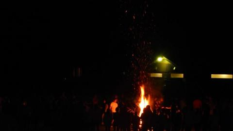 Campers and staff gathered around bonfire.