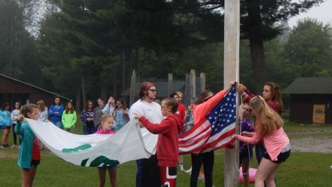 Campers work together with a counselor to raise the American and 4-H flags as the rest of camp looks on.