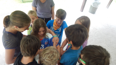 group of campers holding hands in human knot activity.