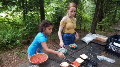 Campers adds sauce to bread in a pie iron with counselor supervision.