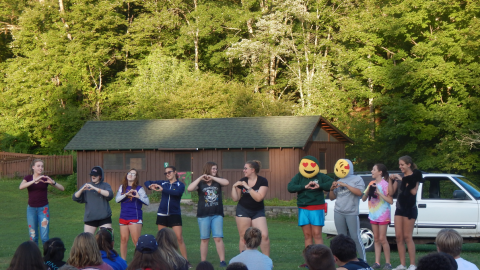 Cabin group stands together in front of camp audience making hearts with their hands. Two youth have emoji pillows in their sweatshirts as if they were their faces.