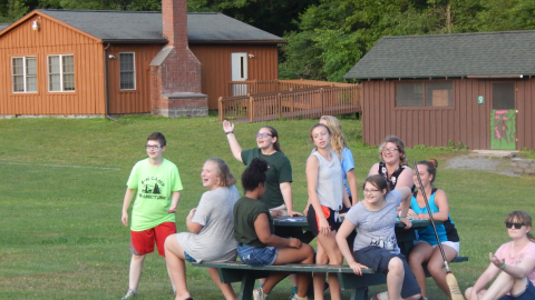 Cabin group seated at a picnic table with counselor who is waving arm.