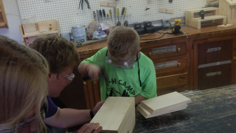 Counselor holds a wood project steady for a camper using a hammer.