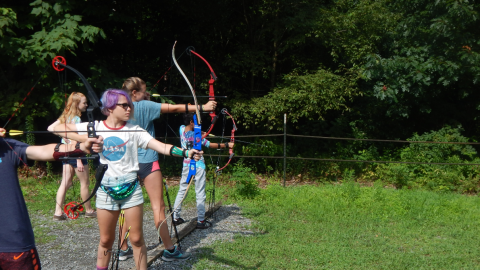 campers standing in a line with bows drawn as a counselor walks behind them.