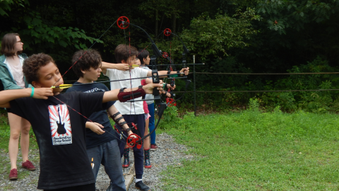 youth stand on the shooting line with bows drawn and a ground quiver of arrows in a ground quiver beside them while a counselor watches over them.