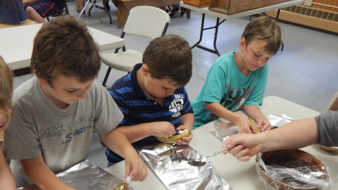 youth putting marshmallows and chocolate chips into a sliced banana over tin foil while seated around a table.