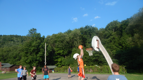 camper jumping up to dunk a basket on the bball court while others watch.