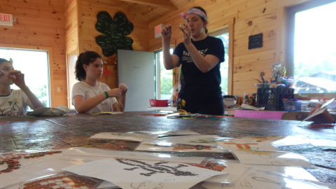Craft director demonstrates beading technique to a group of campers seated around the table. Patterns they can choose to make are scattered across the table including a skunk, football, and many more.