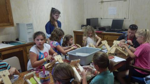 campers gathered around a table stringing beads onto wooden looms.