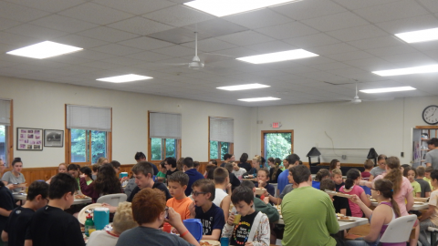 Campers and counselors seated together for a family style meal.