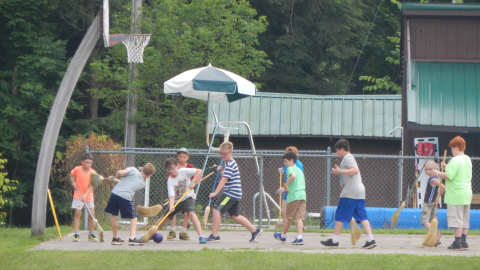group of youth playing broom hockey on the basketball court.