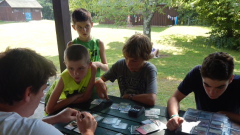 Four youth gathered at a table with one counselor engaged in a game of Magic the Gathering.