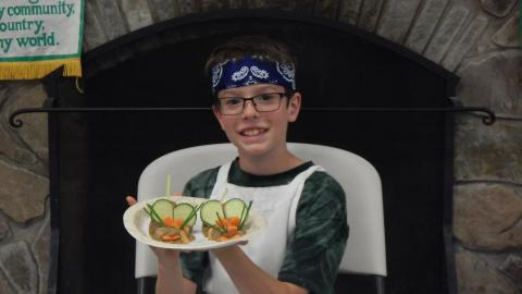 Youth displaying a culinary creation that resembles a mouse made of veggies.