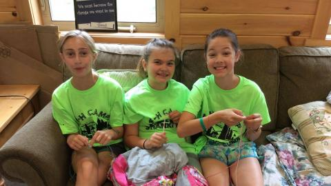 Three youth in matching camp t-shirts sit on the craft hall couch making boondoggles.