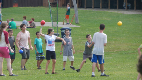 youth throwing foam balls at one station with other groups in the background.